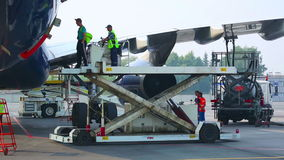 Unloading the luggage. Airport service crew unloading arrived airliner stock video footage