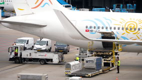 Unloading luggage containers from the aircraft. AMSTERDAM, THE NETHERLANDS - JULY 29, 2017: TUI Airlines Boeing 767 HB-JJF at unloading luggage containers from stock video footage