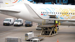 Unloading luggage containers from the aircraft. AMSTERDAM, THE NETHERLANDS - JULY 29, 2017: TUI Airlines Boeing 767 HB-JJF at unloading luggage containers from stock video