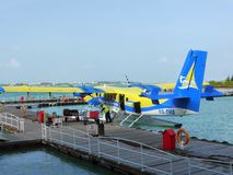 Unloading luggage from floatplane. Unloading luggage from a Trans Maldivian airways DHC Twin Otter seaplane at Male International Airport in the Maldives Royalty Free Stock Photos