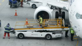 Unloading luggage from a passenger plane stock video footage