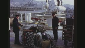 Unloading Luggage At The Port. SPAIN, GRAN CANARIA, LAS PALMAS, NOVEMBER 1972. Three Shot Sequence Of A Cruise Liner Crew Members Unloading Luggage At The Port stock footage
