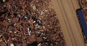 Unloading scrap metal m/s. Metal loaded into wagons by crane, view from above, cover shot stock video