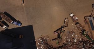 Unloading scrap metal. Several cranes unload scrap from trucks, view from above, cover shot stock video footage