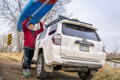 Unloading stand up paddleboard from car roof racks. Fort Collins, CO, USA - April 7,2018: A senior male paddler is unloading his racing stand up paddleboard from Stock Photos