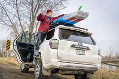 Unloading stand up paddleboard from car roof racks. Fort Collins, CO, USA - April 7,2018: A senior male paddler is unloading his racing stand up paddleboard from Stock Photo