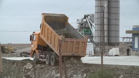 Unloading Truck At Construction Site. Dumper truck unloading soil or sand at construction site or job site on a cloudy day. Orange or yellow dump truck unloading stock video footage