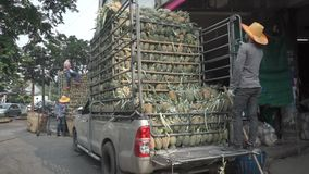 Unloading truck full of pineapples in Bangkok. Clip stock video footage