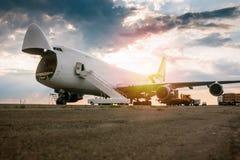 Unloading wide body transport cargo plane in the morning sun. Unloading wide body transport cargo airplane in the morning sun stock photos