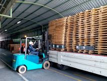 Unloading wood pallet from truck. stock photography