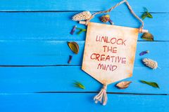 Unlock the creative mind text on Paper Scroll. With dried flower around and blue wooden background royalty free stock photography