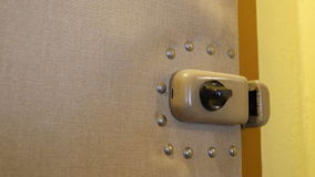Unlock and Lock the Door. A man unlocks and locks the additional safety lock. Audio is included stock video