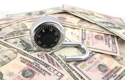 Unlock The Secret to Wealth. A combination lock shot over stack of US Dollars banknotes Stock Images
