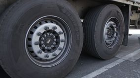 Unlock the wheels of the truck with metal shoe. Worker in overalls removes iron shoe from under the wheels of a truck stock footage