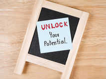 Unlock your potential 5. Handwriting Unlock Your Potential on colorful notepaper and blackboard with wood background. (Business concept Stock Photography