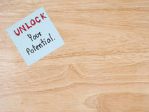 Unlock your potential 8. Handwriting Unlock Your Potential on colorful notepaper with wood background. Business concept Stock Photo