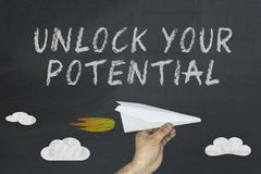 Unlock your potential. Open your mind design. Potential concept business concept. Unlock your potential concept on blackboard. Hand holding paper plane Royalty Free Stock Photo