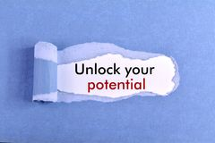 Unlock Your Potential. The text Unlock Your Potential appearing behind ripped blue paper Stock Photography