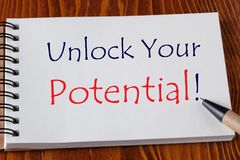 Unlock Your Potential. Written on notebook with pen aside on wooden desk. Business Concept stock photo
