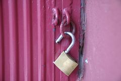 Unlocked brass padlock on a red metal door Stock Images