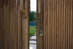 Unlocked metal chain on wooden doors with garden behind. Unlocked metal chain on old wooden doors with green garden and private pool behind Royalty Free Stock Photo