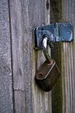 Unlocked padlock hanging from hinge2. Heavy lock is open and hanging free Royalty Free Stock Photography