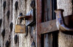 Unlocked. A padlock hangs unlocked on heavy old wooden fortress like door Stock Photo
