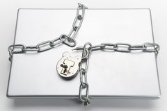 Unlocked padlock and laptop. Opened padlock with key and chain wrapped around closed laptop computer stock images