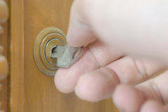 Unlocking cabinet. Closeup of male hand unlocking wooden cabinet Royalty Free Stock Images