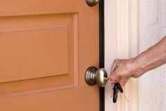Unlocking Door. Homeowner unlocking the front door to his house Stock Photography