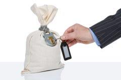 Unlocking a money sack. Businessman unlocking a money sack, white background, blank tag on key fob Stock Photos