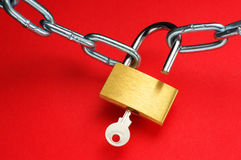 Unlocking padlock. Unlocking padlock and chain on red background Stock Photography