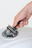 Unlocking petrol cap. Hand unlocking the petrol cap on a white motorcycle Royalty Free Stock Images