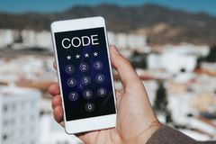Man holding mobile phone with passcode in the screen. Unlocking phone. Stock Photos