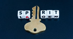 Unlocking the spirit. Text ' spirit ' in black uppercase letters on white cubes with the letter ' i ' replaced by a large gold key on a dark background Stock Photo