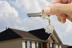 Unlocking Your Door. A key on a house keychain in a persons hand on a house and sky background, unlocking your door Royalty Free Stock Photos