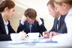 Unlucky day. Image of frustrated businessman touching his head while his colleagues looking at him at meeting Stock Image