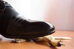 Unlucky day - slipping on a banana peel. Black patent shoe of young man slipped on a banana peel Royalty Free Stock Photos