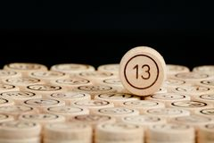 Unlucky number 13 on the wooden barrels lotto. Black background. Close up Royalty Free Stock Images