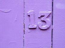 Unlucky purple thirteen. Purple painted door with the number thirteen on it Stock Photos