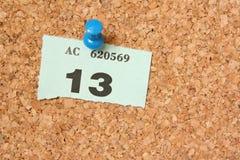 Unlucky Thirteen. Number thirteen ticket pinned to a cork board Stock Photography