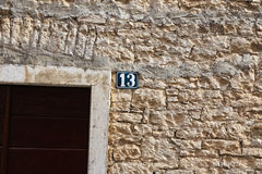 Unlucky thirteen house number sign. On old stone wall Royalty Free Stock Images