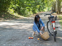 Unlucky woman with spilled apples. Organic apples spilled from the basket on the ground Stock Photo
