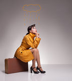 Unlucky yellow. Unlucky beautiful lady sitting on a suitcase on grey background Royalty Free Stock Image