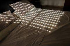 Unmade διπλό κρεβάτι με τα σχέδια κύκλων από το κλειστό παραθυρόφυλλο Στοκ Εικόνα