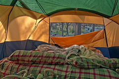 Unmade Airbed Inside Camping Tent. This camping stock photo depicts a used airbed with pillows and blankets and the air flap down to show the campsite royalty free stock image