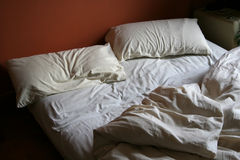 Unmade Bed. With white covers and red background stock photos