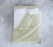 Unmade bed on concrete floor. Top view of an unmade bed with beige blanket and white linens on concrete floor. 3D Rendering Royalty Free Stock Photography
