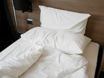 Unmade bed with crumpled duvet, bed sheet and pillows. At the hotel in the morning royalty free stock image