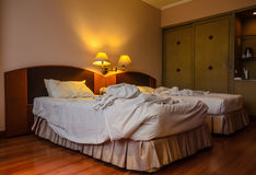 An unmade bed of a hotel room Royalty Free Stock Images
